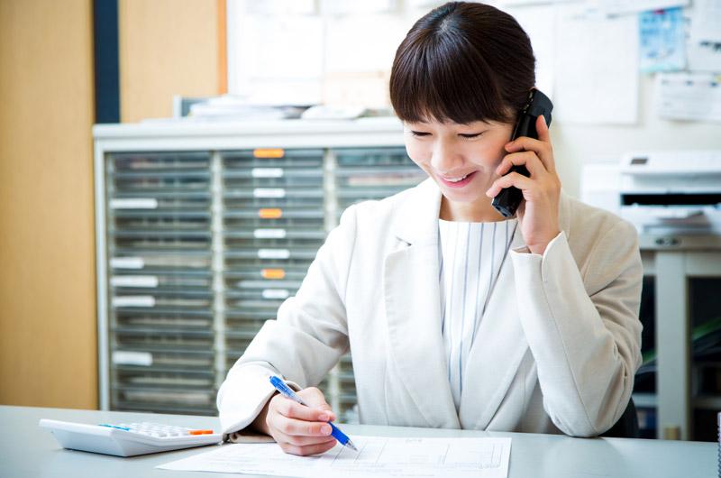 コードレス電話機で通話する女性